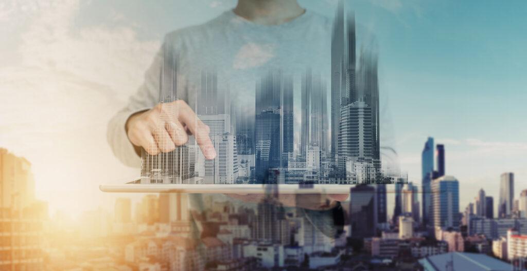 Image of man designing a digital city on a tablet.